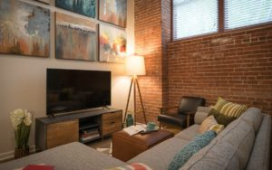 Apartment living room with brick accent wall at Shadyside Commons in Pittsburgh, PA