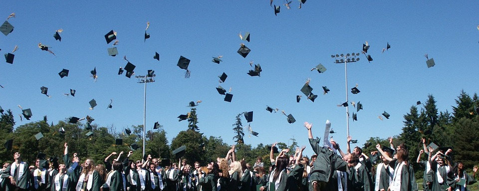 dozens of university graduates throwing caps in the air